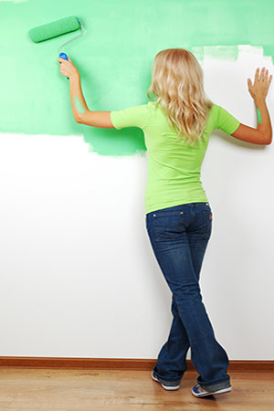woman painting a green screen wall